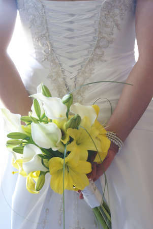 arm bouquet: A young bride holds her flower bouquet behind her back.