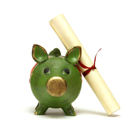 college fund savings: An isolated shot of a piggy bank and diploma scroll for saving for an education.
