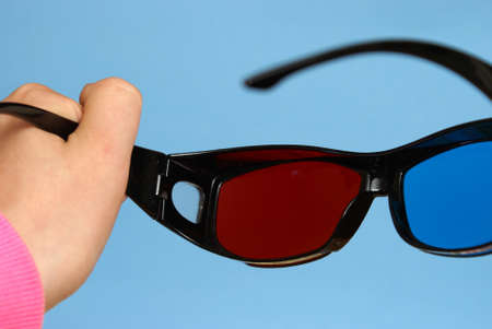visual perception: A woman raises a pair of 3D glasses to put them on her face before the movie.