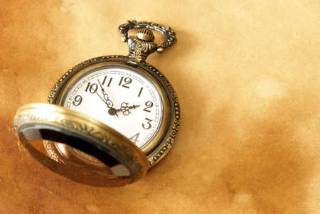 A macro shot of a pocket watch on some aged paper background. Stock Photo