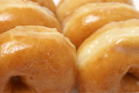A macro shot of a box of sugar glazed donuts ready for consumption.