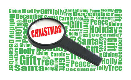 A magnifying glass highlights the word Christmas that surrounds corresponding words to the holiday season. photo