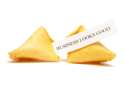 A cracked open fortune cookie stating that business looks good. photo