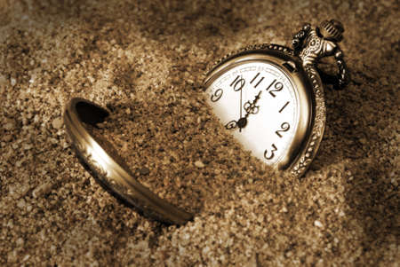 bury: A pocket watch is buried in the dirty sand.