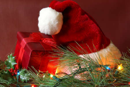 A red present and santa hat in a nice Christmas season setting. photo