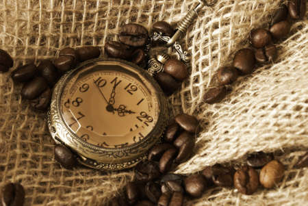 A handful of coffee beans on some burlap with an antique pocket watch. photo