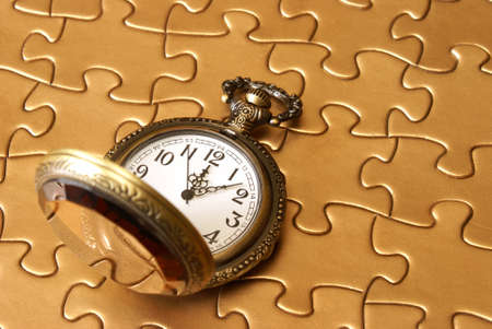 A pocket watch rests on a golden puzzle. Stock Photo - 10566493