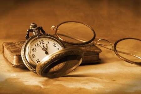 reloj antiguo: Un antiguo reloj de bolsillo, las gafas y la biblia se unen en esta época la naturaleza muerta. Foto de archivo