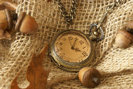 sackcloth: A pocket watch on some burlap with dead oak leaves and acorns for the changing of the autumn season.