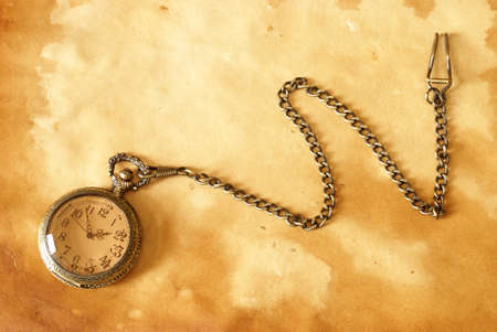 A pocket watch with a chain on a brown background.
