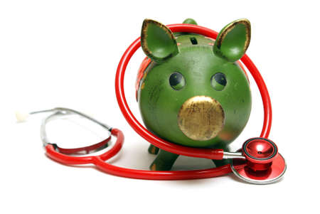 health care funding: A piggy bank and stethoscope are isolated on white and give representation to an emergency fund.