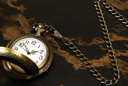 A pocket watch with a chain on a marble background. photo