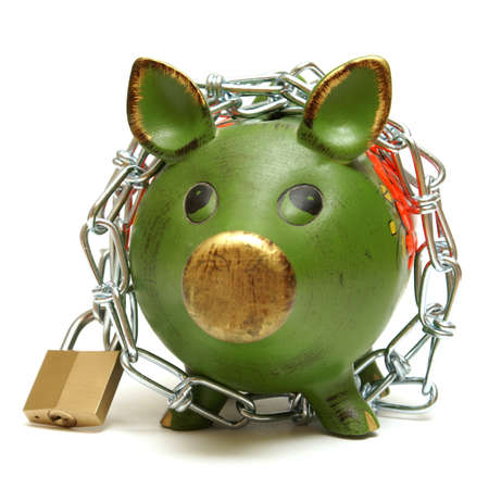 A conceptual shot of an isolated piggy bank that is bound by chains to give representation to protecting your money. Stock Photo - 10959230