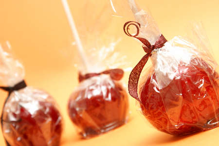 treating: Three red candy apples in plastic wrappers ready for treating the sweet tooth. Stock Photo