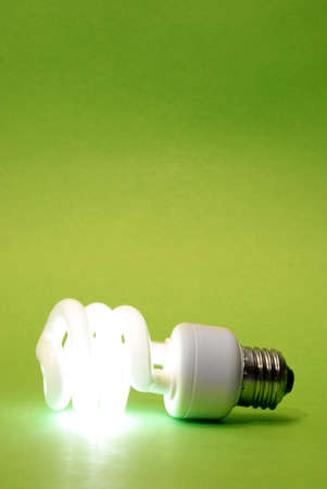 A modern eco friendly light bulb that is abstractly lit with a green background. photo