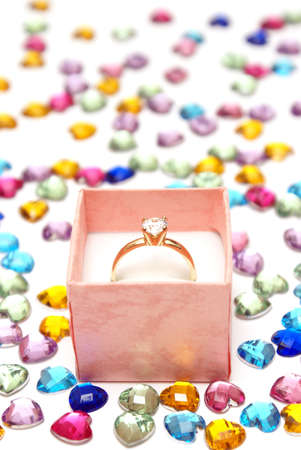 A diamond ring in a pink jewelry box that is surrounded by colorful heart shaped rhinestones. photo