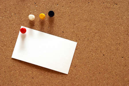 A pushpin is holding a blank notecard on a cork board. photo