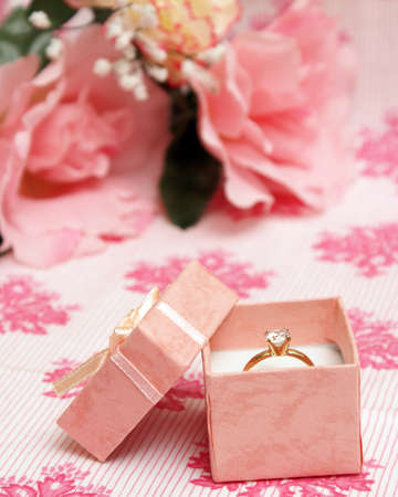 A beautiful diamond ring in a pink jewelry box.