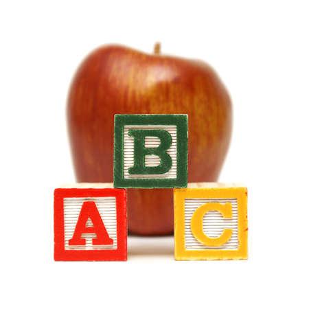comida inglesa: Tres bloques de aprendizaje se apilan frente a una manzana de color rojo agradable para la mente de los j�venes en el trabajo. Foto de archivo
