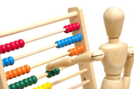 abacus: Manekin pozycjonuje kilka kulek na liczydle, aby rozwiązać swój matematyki.