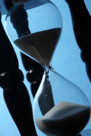 The sands of time trickle through this blue toned hourglass.