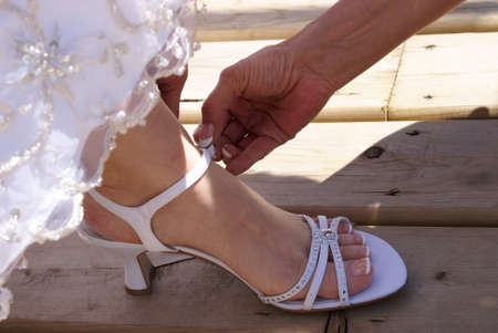 A bride is being helped with putting her shoes on. photo