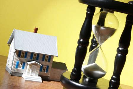 Una casa modelo y el reloj de arena se unen para varios conceptos. Foto de archivo