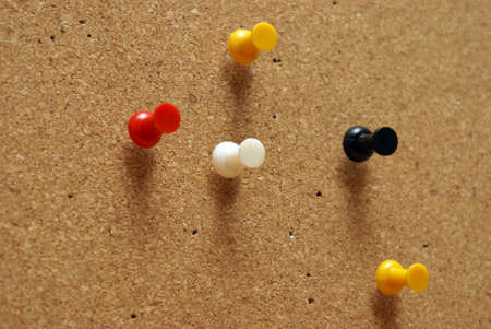 corkboard: Various pushpins inserted on a cork board.