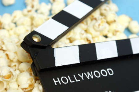 A movie clapboard rests on a pile of fresh popcorn.