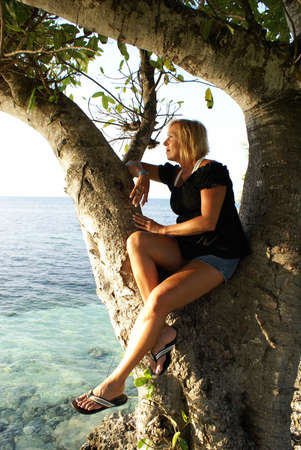 mujer mirando el horizonte: Una mujer está mirando sobre el océano mientras está sentado en un gran árbol.