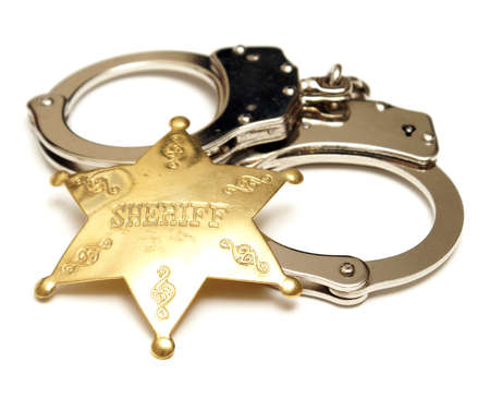 sheriff: An isolated shot of a sheriff badge and pair of handcuffs.