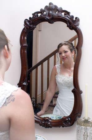 A newly married bride is admiring herself in the mirror on her wedding day. 版權商用圖片
