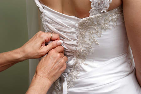 tight fitting: A bridesmaid helps the bride get ready by fastening her dress up in the back.