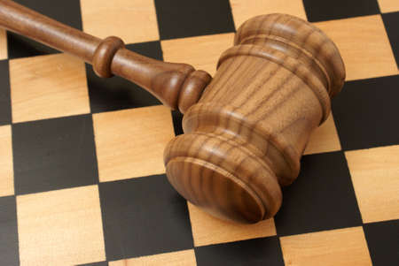 auction win: A wooden gavel and chess board represent strategy in legal situations.