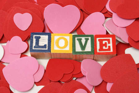 Alphabet blocks spell out the word love which is surrounded by foam heart shapes. Stock Photo - 11875434