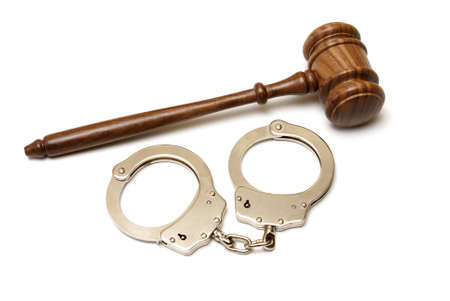 restraints: A pair of handcuffs and gavel are isolated for legal concepts. Stock Photo