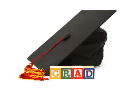 A grad hat with alphabet blocks are isolated on white. photo