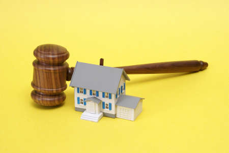 A gavel and model house represent a few legal and auction concepts. photo