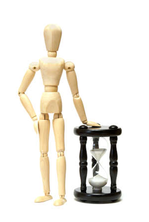A wooden mannequin stands next to an hourglass for many time concepts. photo