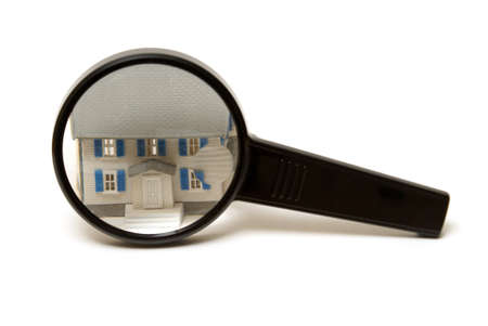 A home inspection concept using a model house and a magnifying glass. photo