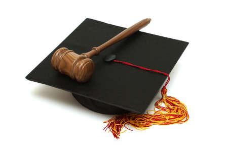 derecho penal: Un birrete y martillo se encuentran aislados de los licenciados en derecho.