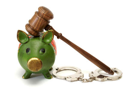 A pig bank, handcuffs, and a mallet represent legal expense concepts. Stock Photo - 12365338