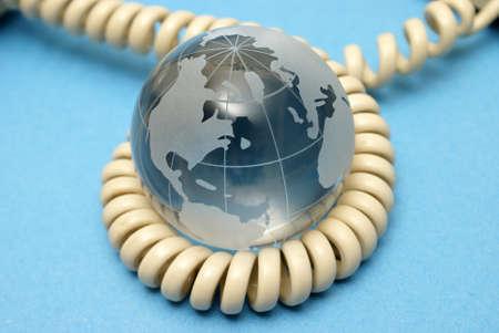 A globe and phone cord represent global communications. Stock fotó