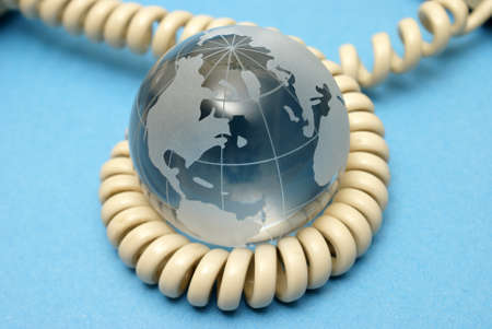 international internet: A globe and phone cord represent global communications. Stock Photo
