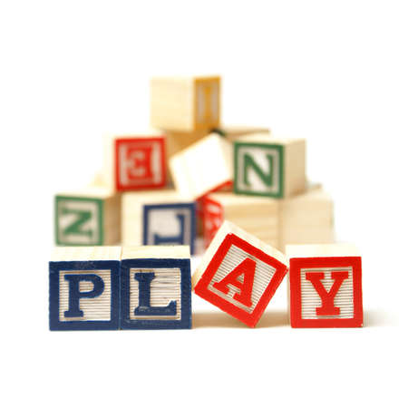 The word play has been spelled out while playing with toy blocks. Stock Photo