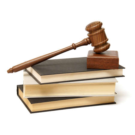 An isolated pile of books with a wooden gavel resting on top.