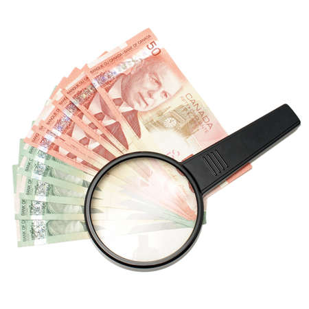 50 dollar bill: A magnifying glass on top of spread out Canadian money. Stock Photo