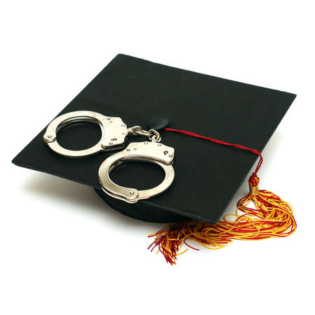 A mortarboard and pair of handcuffs are isolated for police graduates.