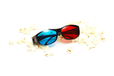 A pair of sleek 3D glasses rests on top of a pile of fresh popcorn. photo