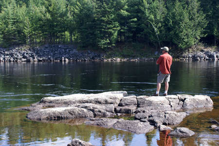 reflection: A fisherman stands on some rocks as he reels in his lure.